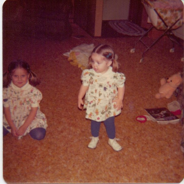 A picture of me at 2 years old. I am standing up wearing a Winnie the Pooh dress with blue tights. My ahir is in pigtails, and I'm looking at something off camera.