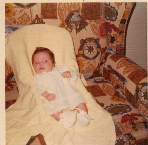 A picture of me at 3 months old laying on a 1970s style couch.